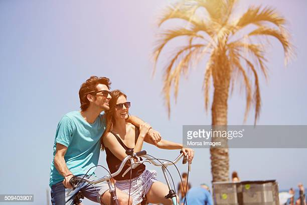 Man with arm around woman riding bicycle