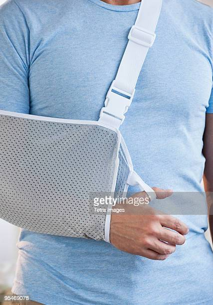 man with arm in sling - arm sling stock pictures, royalty-free photos & images