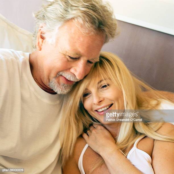 Man with arm wrapped around woman's shoulder