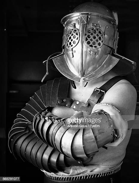 Man With Arms Crossed In Warrior Costume Against Black Background