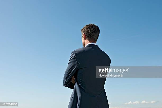 man with arms folded looking into distance - 後ろ姿 ストックフォトと画像