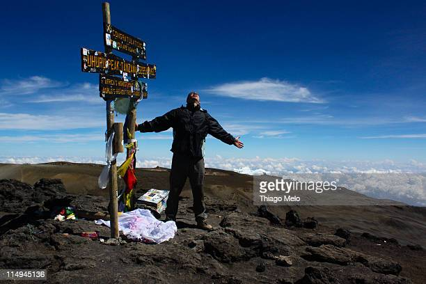 Man with arms open in Kilimanjaro summit