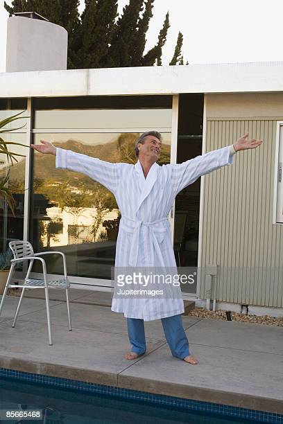 Man with arms outstretched by swimming pool