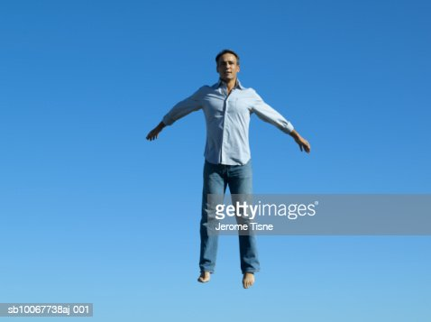 Man With Arms Outstretched Floating In Air Stock Photo