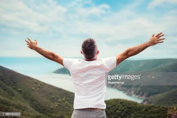 mann mit ausgestreckten armen auf bergspitze - ausgestreckte arme stock-fotos und bilder