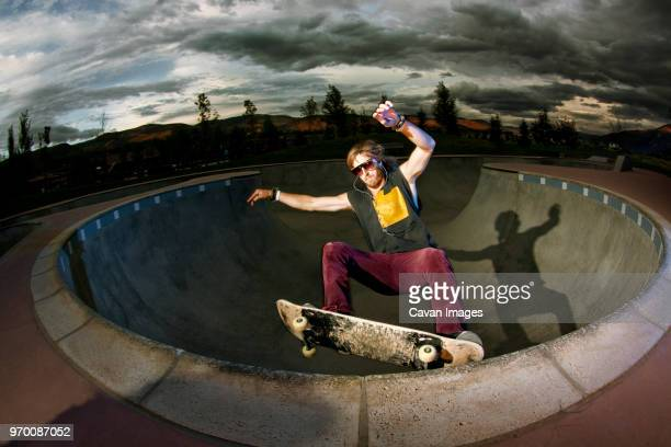 Man with arms outstretched skateboarding in skateboard park