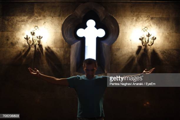 Man With Arms Outstretched Standing Against Cross In Illuminated Church