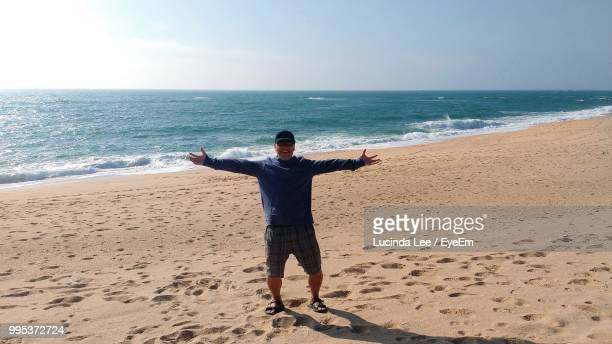 man with arms outstretched standing at beach against sky - lucinda lee stock photos and pictures