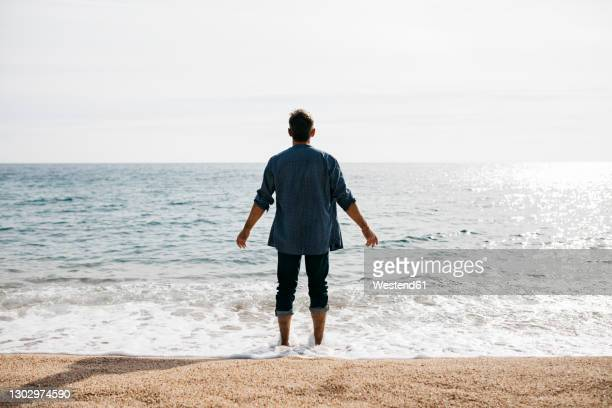 man with arms outstretched standing at water's edge against clear sky - arms outstretched stock pictures, royalty-free photos & images