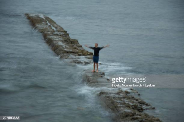 Man With Arms Outstretched Standing On Groyne Amidst Sea