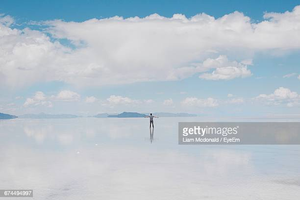 man with arms outstretched standing on salt flat against cloudy sky - nevada stock-fotos und bilder
