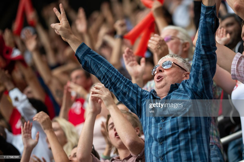 Man with arms raised in a stadium crowd : Foto stock
