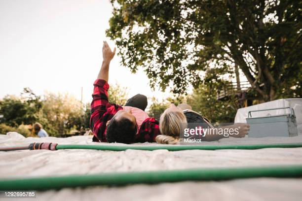 man with arms raised resting by partner after renovating during summer - sweden stock pictures, royalty-free photos & images