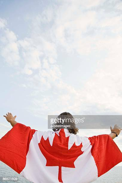 Man with arms raised wearing Canadian flag