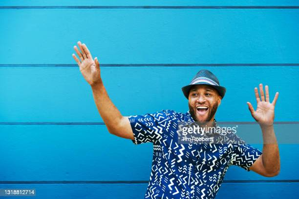 man with arms up, big smile, next to blue wall - beard stock pictures, royalty-free photos & images
