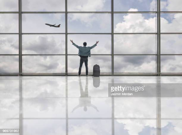 Man with arms up on airport looking at airplane flying