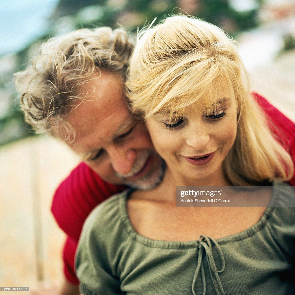 Man with arms wrapped around woman's waist from behind and chin resting on her shoulder : Stockfoto