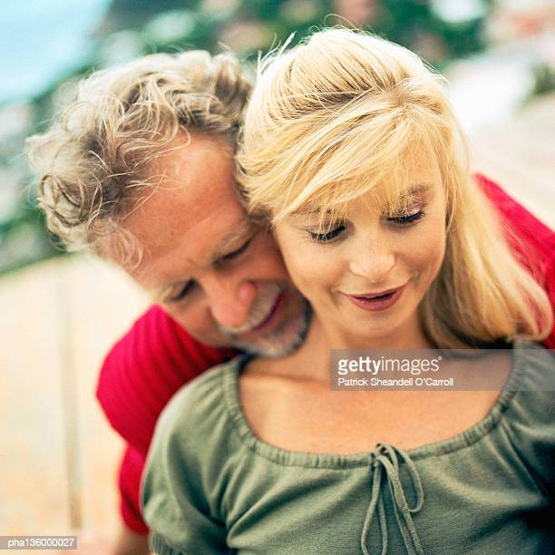 Man with arms wrapped around woman's waist from behind and chin resting on her shoulder