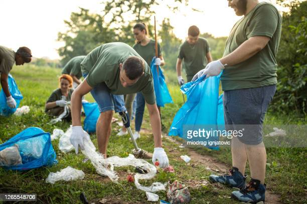 man with artificial leg, cleaning public park with other volunteers - altruism stock pictures, royalty-free photos & images