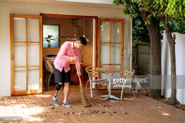 man with artificial leg sweeping leaves in back yard - broom sweeping stock pictures, royalty-free photos & images