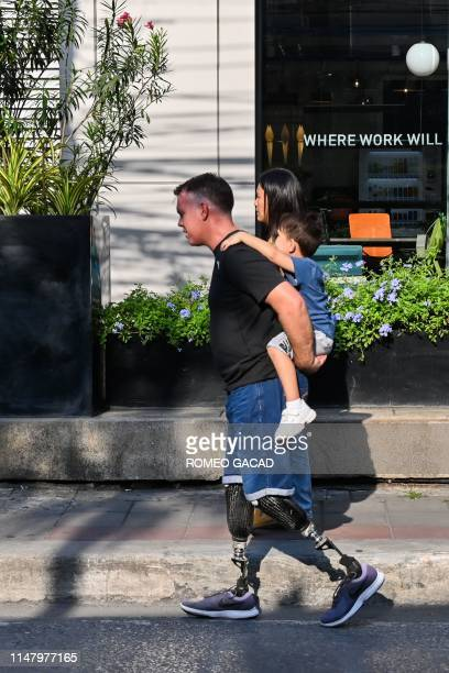 A man with artificial legs carries a child on his back while followed by a woman as they walk along a street in Bangkok on June 4 2019