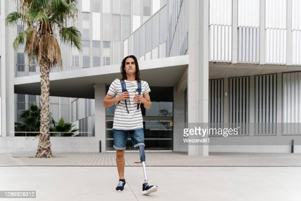 man with artificial limb walking against building in city - 20 24 years stock pictures, royalty-free photos & images