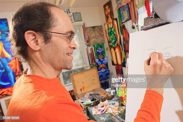 Man with Aspergers drawing his outline for his painting in his art studio