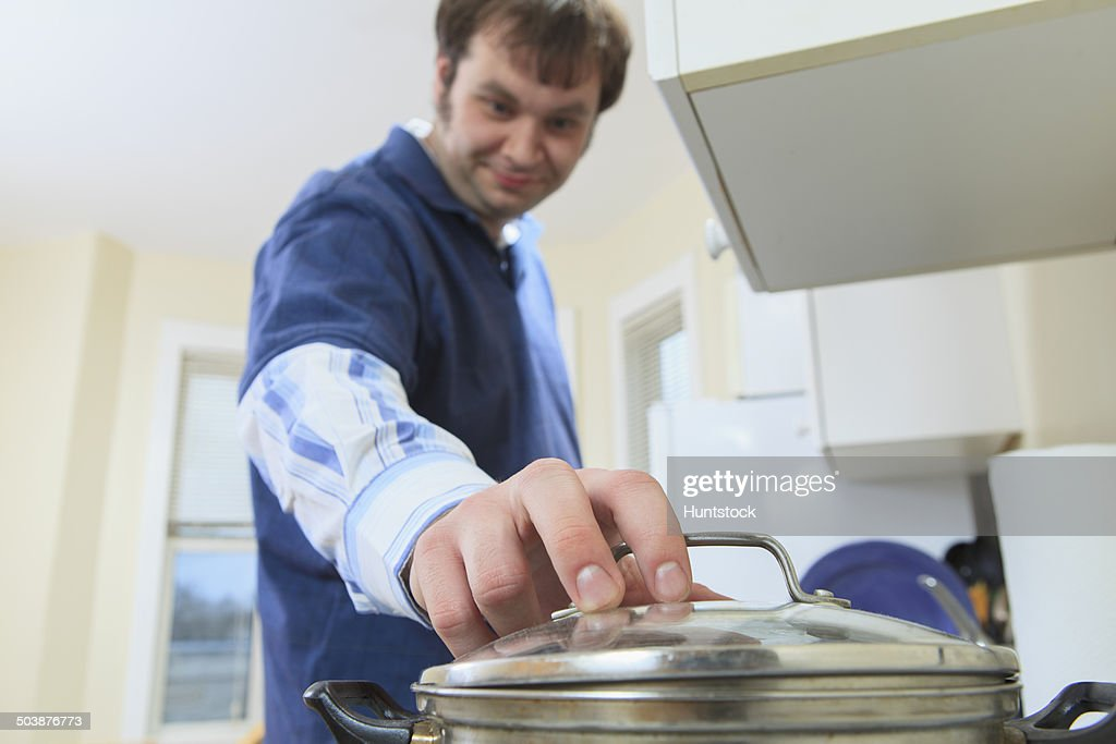 Man with Aspergers living in his home and cooking : Stock Photo