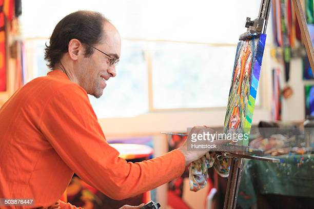 man with aspergers painting in his art studio - autism stock pictures, royalty-free photos & images