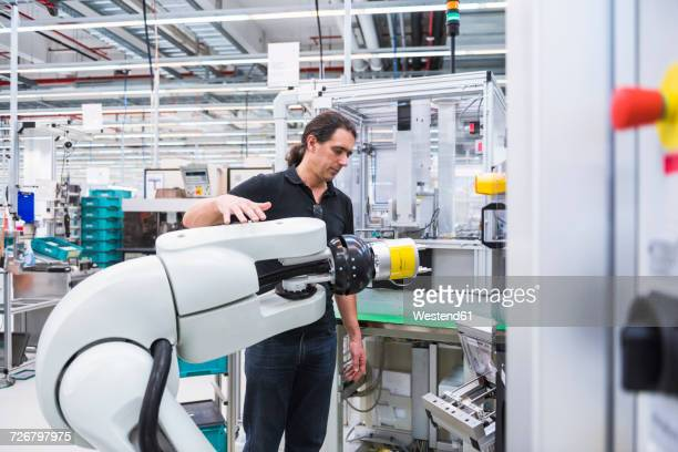 Man with assembly robot in factory