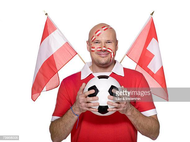 Man with Austrian flag painted on face, holding football, flags aside, smiling, portrait