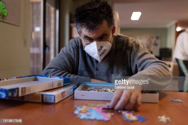 Man with Autism spectrum disorders prepares a puzzle inside at the Paradigma Social Cooperative on April 20, 2021 in Turin, Italy. The Paradigma...