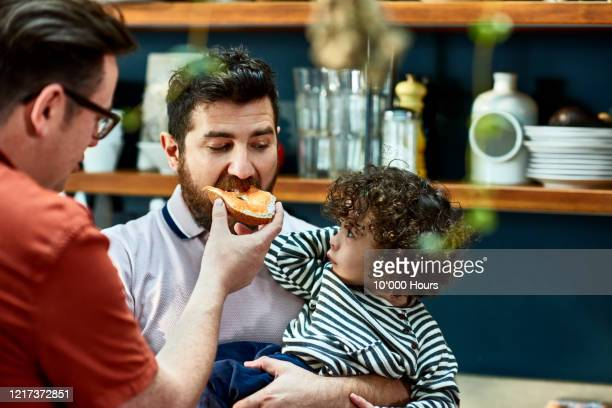 man with baby son being fed a bagel by husband - baby stock pictures, royalty-free photos & images