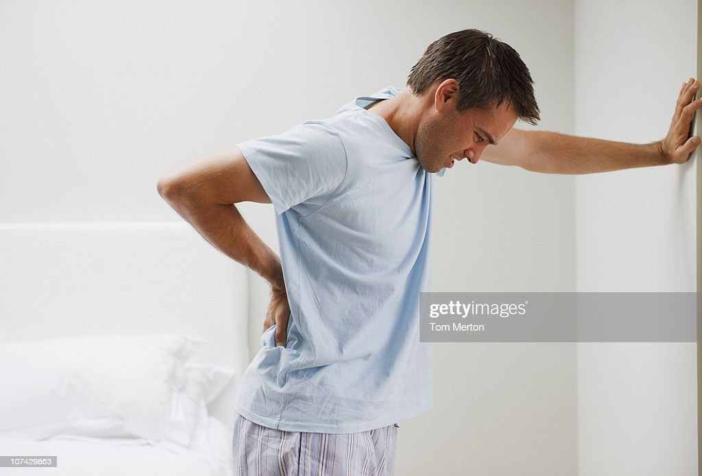 Man with backache leaning against wall : Stock Photo