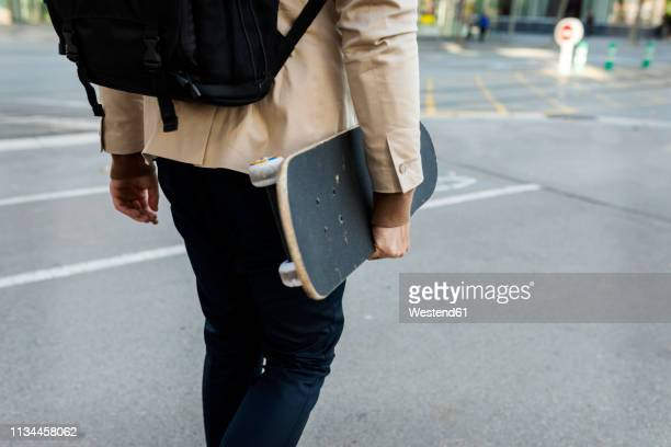man with backpack and skateboard in the city, partial view - mittlerer teil stock-fotos und bilder