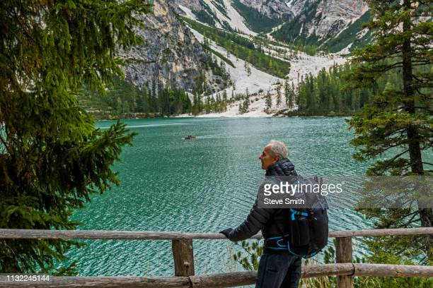 man with backpack at pragser wildsee in south tyrol, italy - pragser wildsee stock pictures, royalty-free photos & images