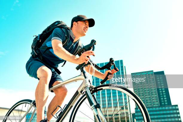 Man with backpack commutes to work on bicycle and rides past office buildings