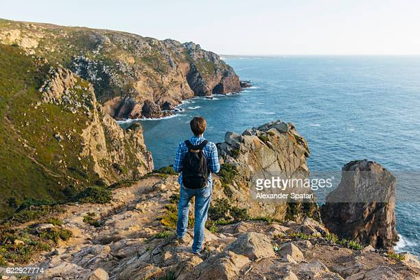 man with backpack hiking along the cliffs of cabo da roca, sintra, portugal - sintra stock pictures, royalty-free photos & images