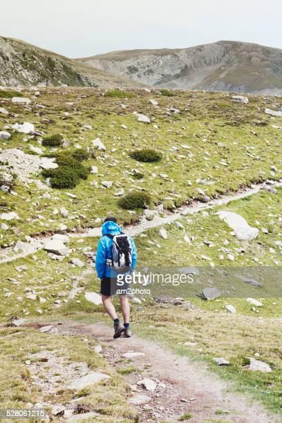 Man with backpack hiking on mountain ridge