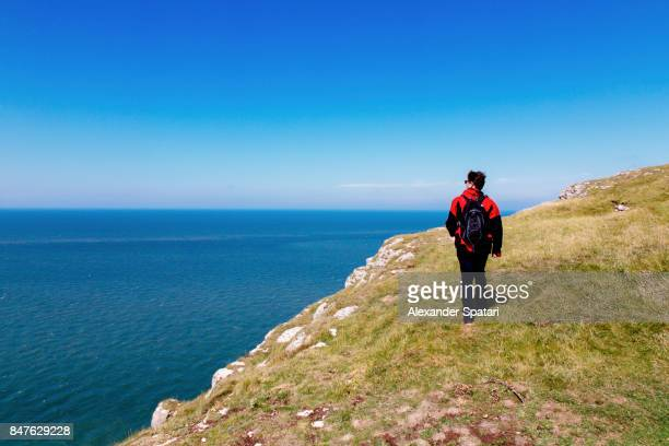 Man with backpack hiking on the hills along the seashore, Wales, United kingdom