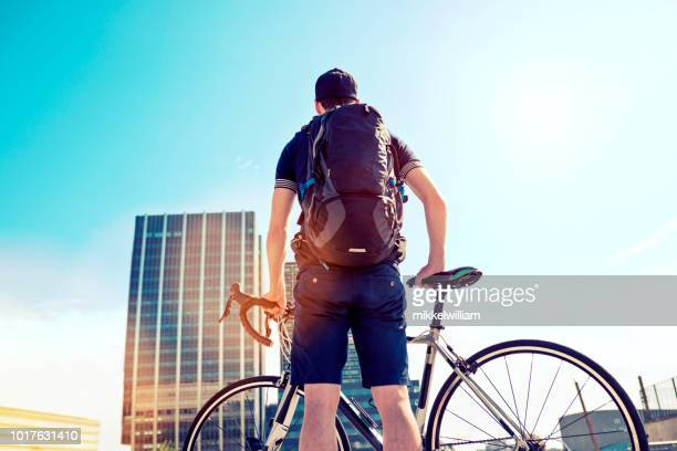 Man with backpack holds on to racing bicycle and looks at office buildings on his commute
