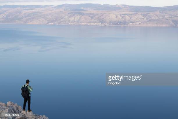 man with backpack looking at sea from the top of the island - adriatic sea stock pictures, royalty-free photos & images