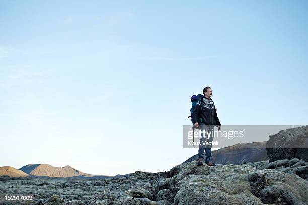 Man with backpack looking out at lava landscape