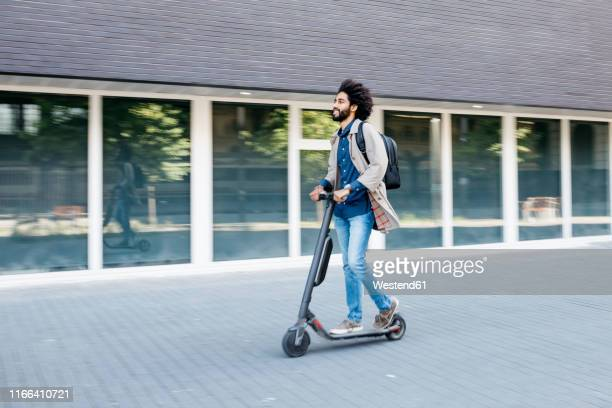 man with backpack riding fast with his e-scooter in the city - être en mouvement photos et images de collection