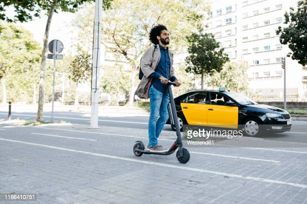 man with backpack riding his e-scooter on a bicycle lane - electric scooter stock pictures, royalty-free photos & images