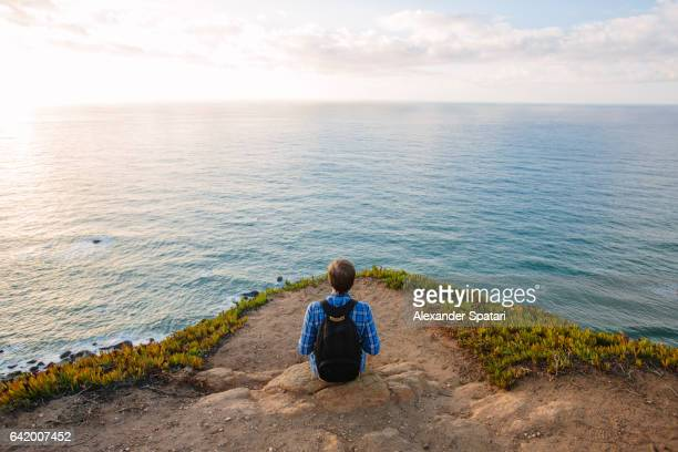 man with backpack sitting at the edge of a cliff and looking at the ocean in cabo da roca, sintra, portugal - 崖 ストックフォトと画像