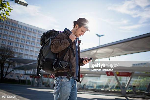 Man with backpack text messaging next to bus stop
