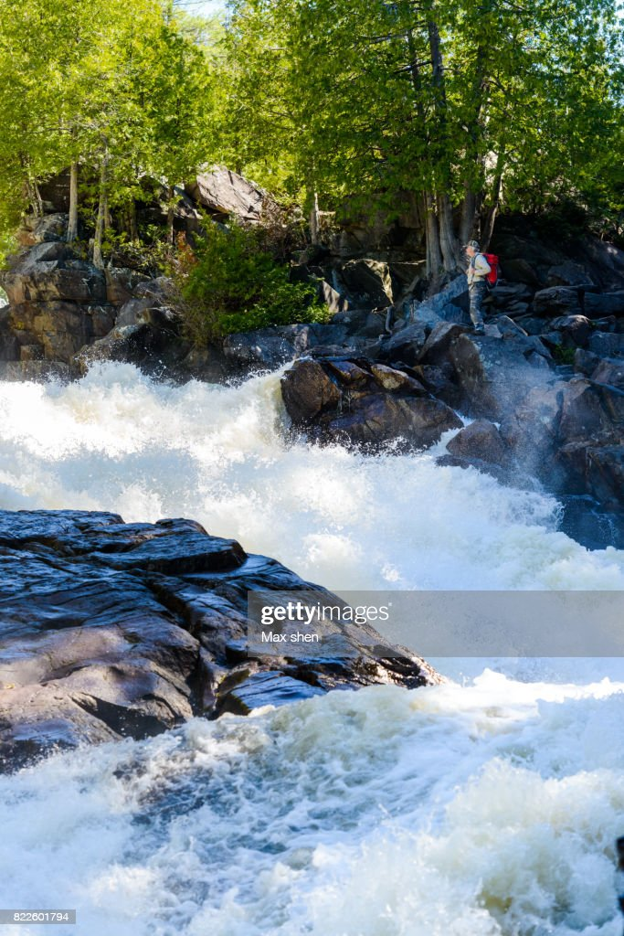 Man with backpack trekking near the streaming gorge : Stock Photo