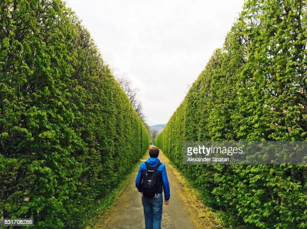 man with backpack walking forward in a green tunnel - fluchtpunkt stock-fotos und bilder