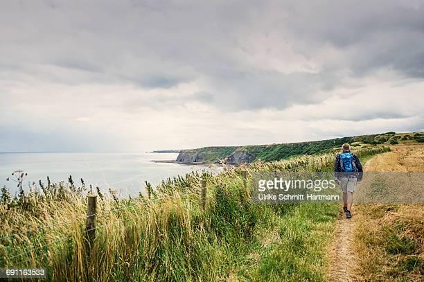 Man with bagpack walking along coastal path